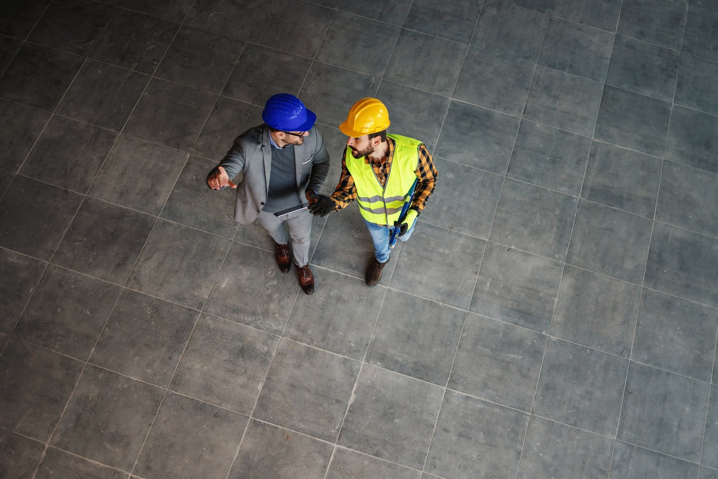 Two men wearing hard hats walk through a room together while talking