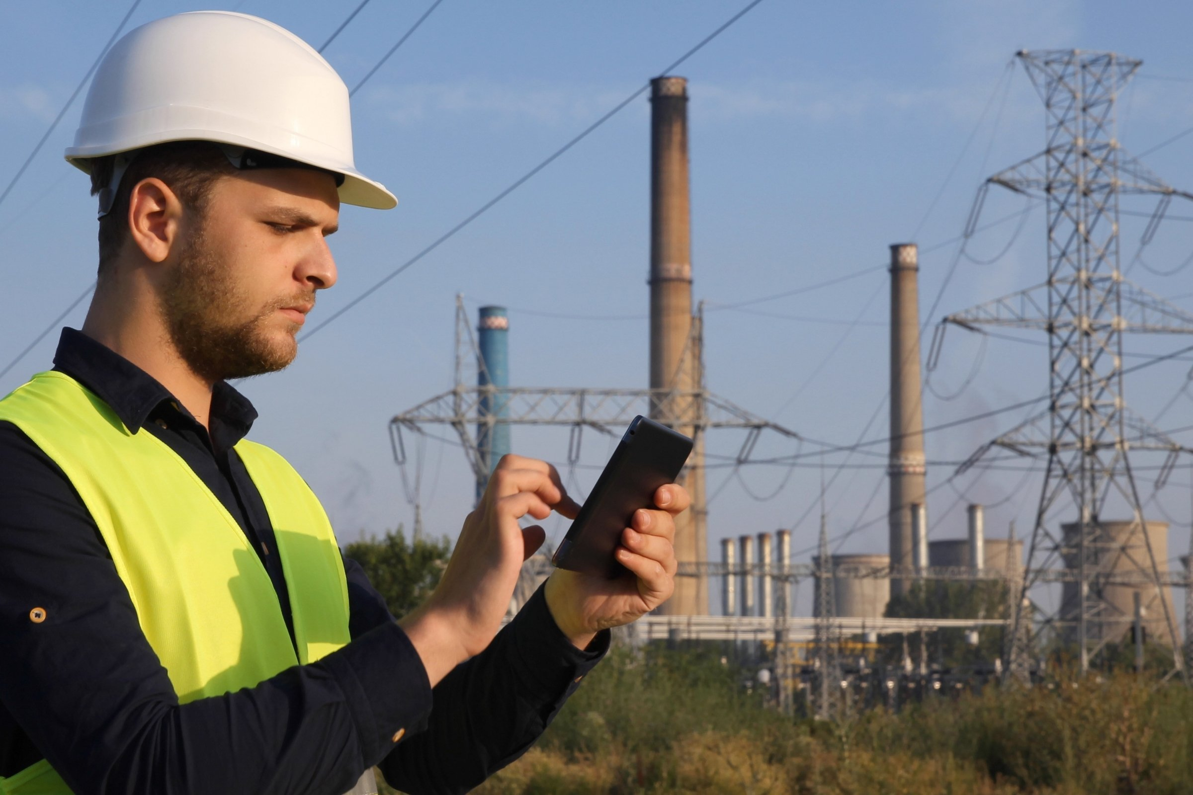 Photo of a man in a hard hat and high vis vest entering information on his phone with a power station in the background
