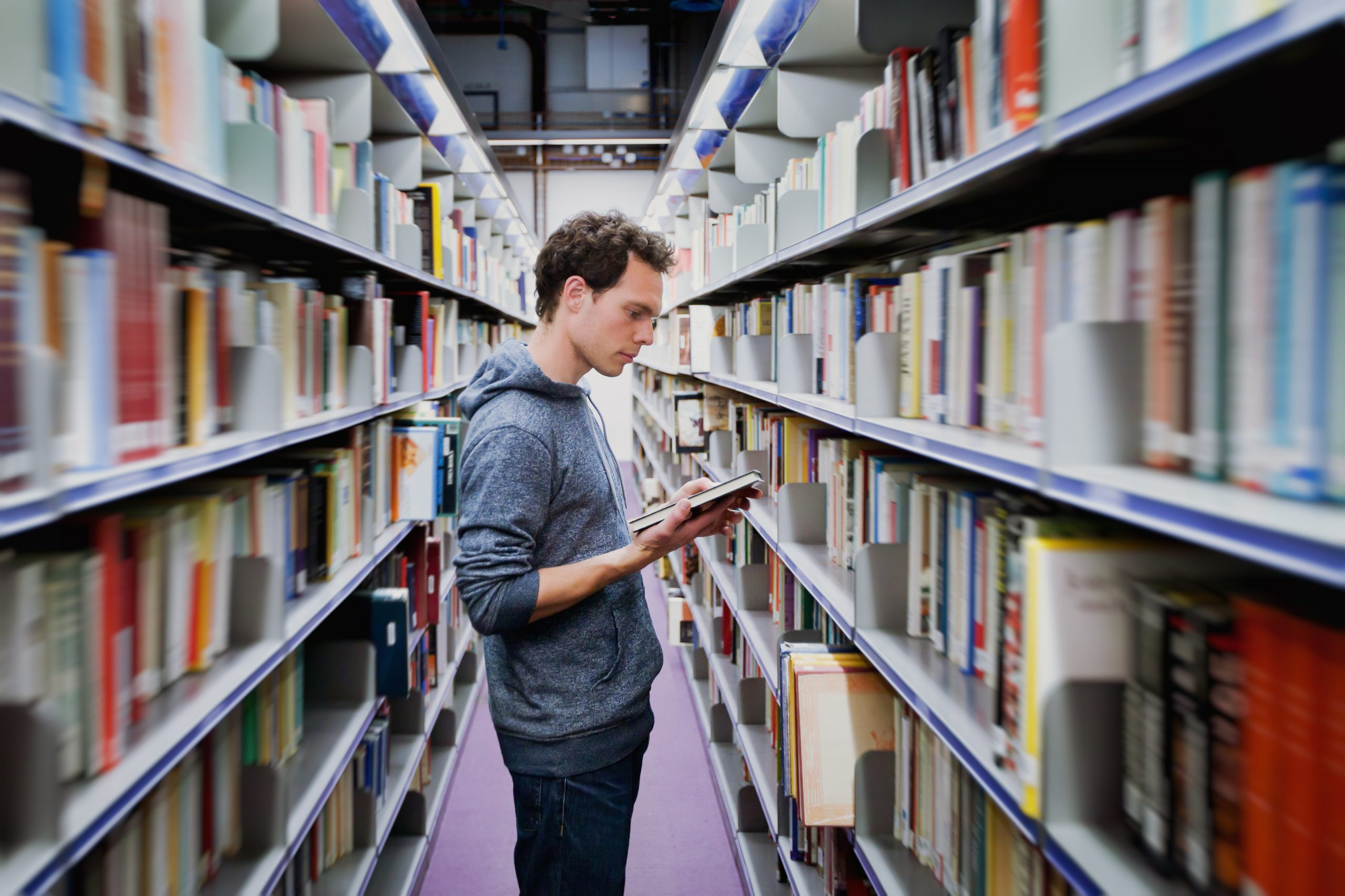 Student stands between long library bookshelves reading a book