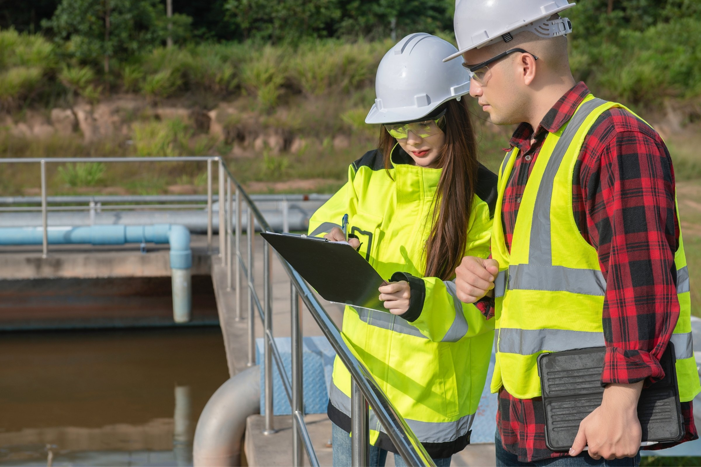A man and a woman in PPEstand on a gangway above a water treatment facility checking things off on a clipboard